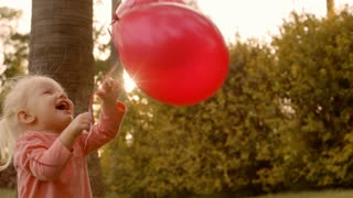 Little girl playing with balloons in park