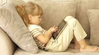 Little girl plays a game on the tablet and nervous