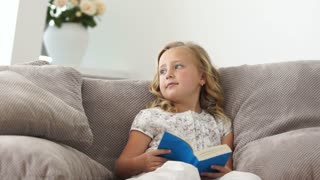Little girl reading a book on the couch