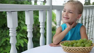 Little girl sitting at the table and clapping. Basket of grapes is on the table