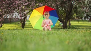 Little girl sitting in garden with umbrella and smiling