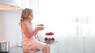 Little girl sitting on table and holding plate of fruit yoghurt