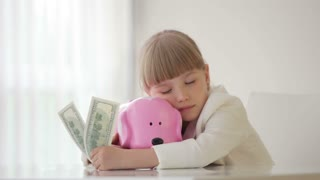Little girl sitting with a piggy bank and falls asleep
