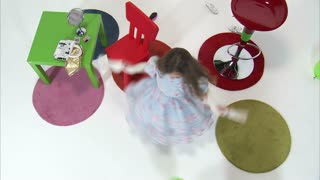 Little Girl Spinning as Twin Kicks Balloons