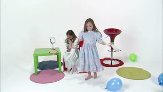 Little Girl Spinning while Her Twin Puts on Makeup