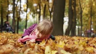 Little girl tumbles in the yellow autumn leaves. Autumn leaf fall. The child lying on the ground looking at the camera and laughing