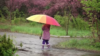 Little girl with an umbrella in the rain in the park. Child spinning with an umbrella in his hand