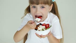 Little girl with fruit yogurt looking at camera and laughing