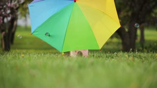 Little girl with umbrella hiding and peeking