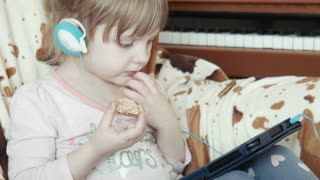 Little pretty cute girl with earphones using digital tablet, watch some video on the intenet