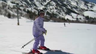 Little Skier Dressed In Pale Purple Snowsuit