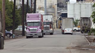 Loaded Trucks Leaving Busy Industrial Mill Complex