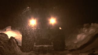 Loader on Snowy Road Moves Away During Snowstorm