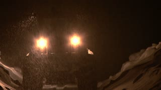 Loader on Snowy Road Moves in Reverse During Night Snowstorm