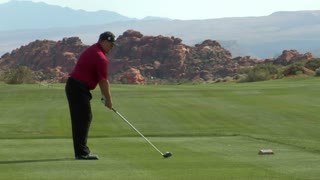 Long Lens Slow-motion Shot Of Man Teeing Off On Red Rock Golf Course
