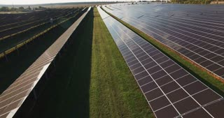 Long rows of photovoltaic panels at a solar farm for converting the energy of the sun to electricity in a concept of renewable energy and natural resources