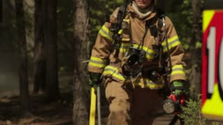 Long Shot Of Firefighter With Hatchet And Fire Hose