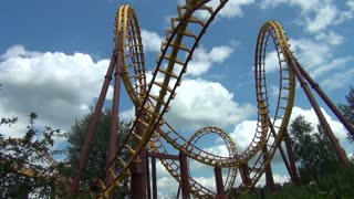 Long Shot of Roller Coaster Loops and Clouds in Distance
