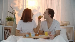 Lovely couple having breakfast in bed: they eating croissants and drinking orange juice