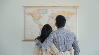 Lovely couple hug and talk about travel plans pointing checkpoints on big world map poster hanged on wall. Attractive brunette and bearded man weared plaid shirts, back shot