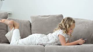 Lovely girl lying on the sofa with a tablet pc