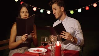 Loving young couple choosing food off a menu as they enjoy a romantic dinner at a restaurant to celebrate Valentines Day