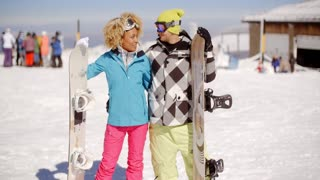 Loving young couple with their snowboards
