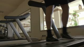Low angle shot of man training on treadmill with only feet to be seen. Gym in the hotel with hall view