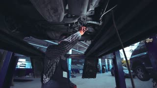 Low angle view of black auto mechanic with red gloves and striped shirt using VR googles and camera on monopod
