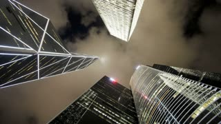 Low angle view of clouds moving over tall office buildings including the Bank of China, Central, Hong Kong, China, T/lapse