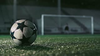 Low angle view of feet of soccer player kicking wet ball on misty grass in the night stadium in slow motion