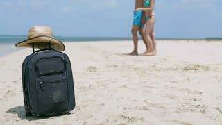 Luggage lying on the beach and couple walking in background, steadycam shot