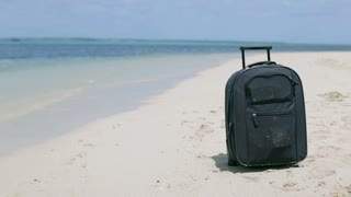 Luggage lying on the beach and woman walking in background, steadycam shot