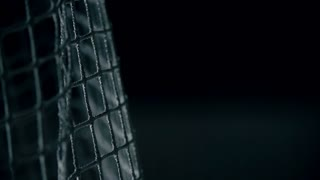 Macro shot of puck flying into gates in slow motion