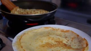 Making Pancake, Crepes on Frying Pan. Closeup.