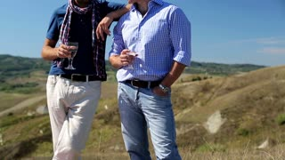 Male friends standing on hill with wine and pointing at something