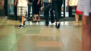 Mall entrance and unrecognizable people walking in and out. Slow motion video