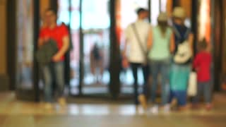 Mall entrance and walking in and out customers. Slow motion blurred bokeh video