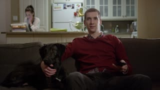 Man and dog watching TV together
