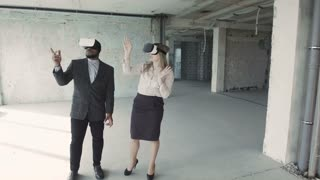 Man and woman discussing future interior of room in unfinished building in oculus rift goggles