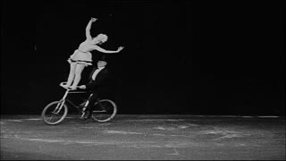Man and Woman Doing Tricks on Bicycle