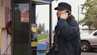 Man Aruging and Hanging Up Payphone