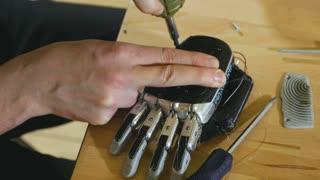 Man assembling innovative cybernetic bionic arm. Hi-tech innovative prosthetics