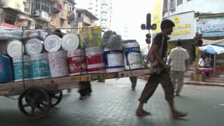 Man Carrying Cart Through Busy Street in Mumbai