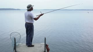 Man Casting Fishing Rod Off Dock Wide Shot
