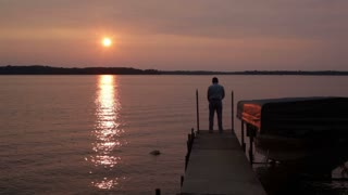 Man Casting off Dock at Sunset