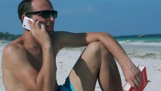 Man chatting on cellphone on the beach