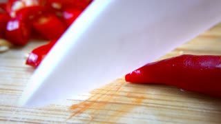 Man Cutting Chili on Cutting Board with Ceramic White Knife - Macro Close Up 4K
