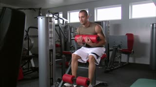 Man Doing Sitting Curls in Gym Weight Room