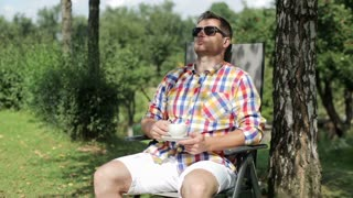 man drinking coffee in the garden